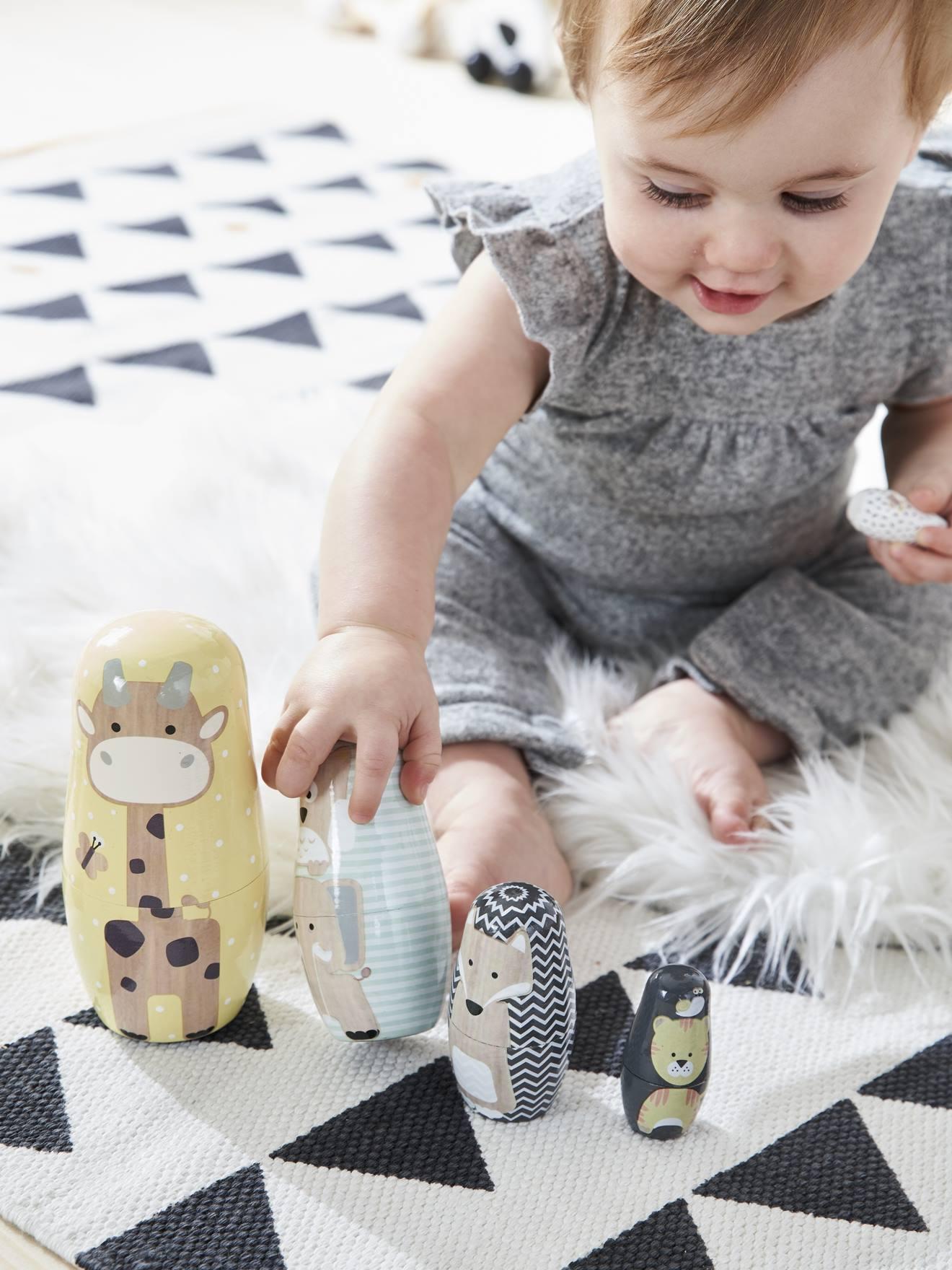 petite fille joue avec boites animaux gigogne en bois