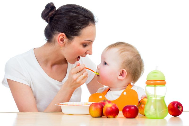 bébé mange avec so,n assistante maternelle