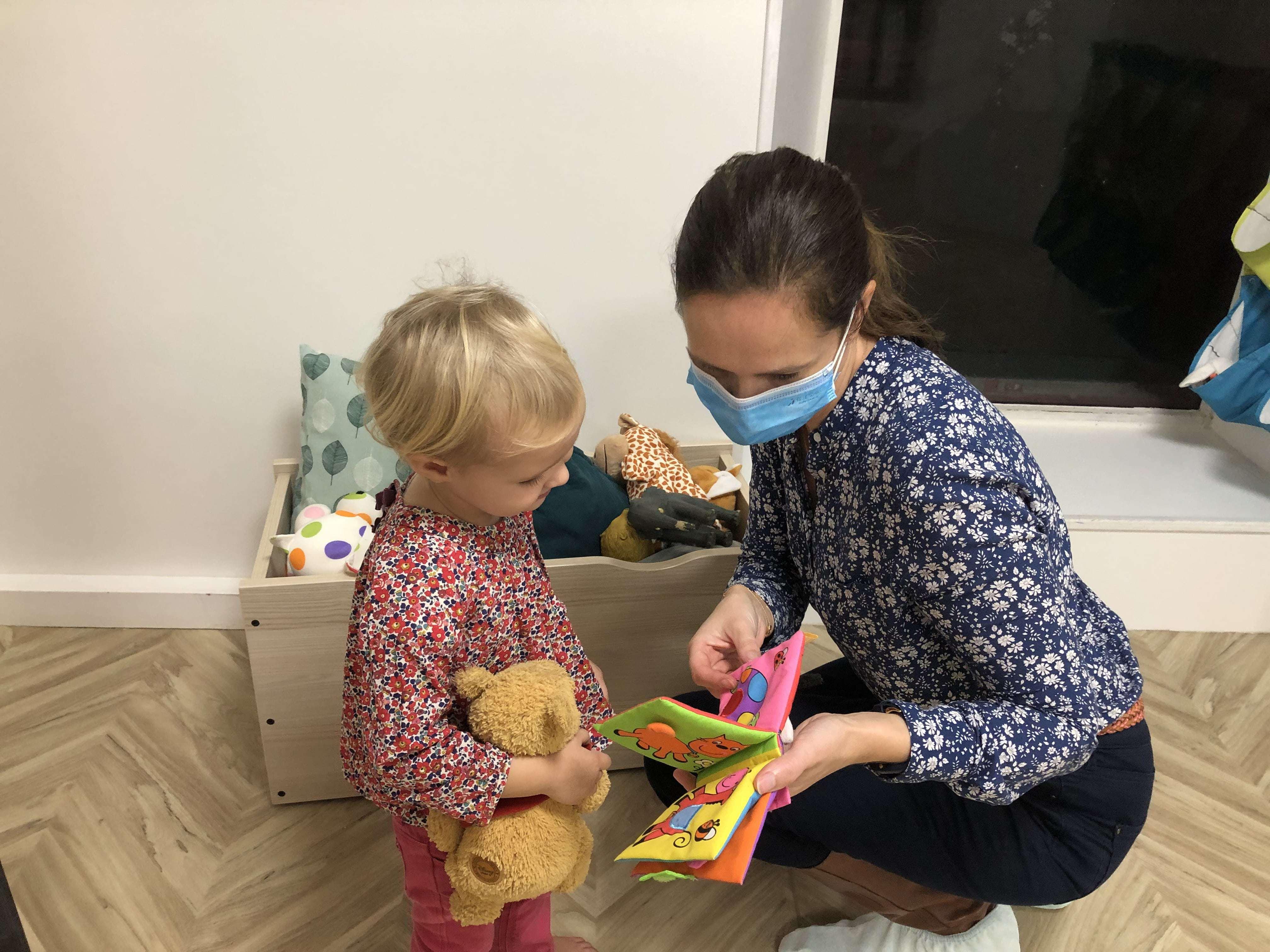 pro de la petite enfance avec un masque et enfant