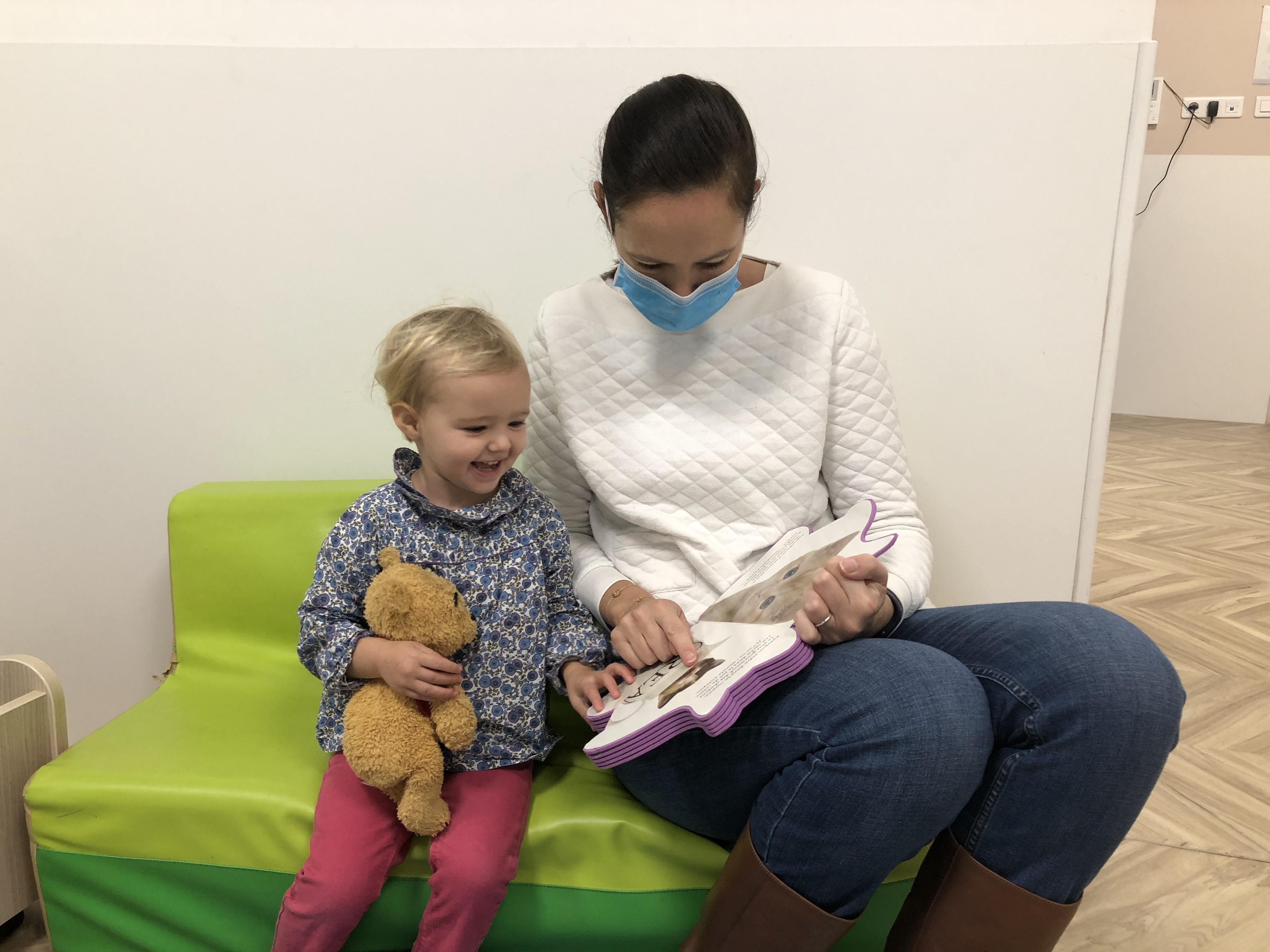 dans une crèche une pro masquée lit un livre à une petite fille