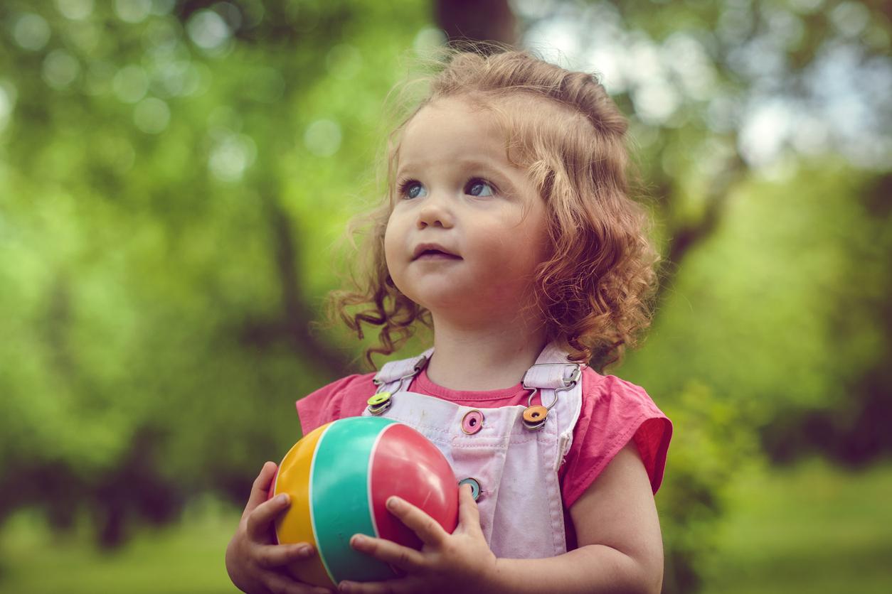 petite fille joue dehors avec un ballon