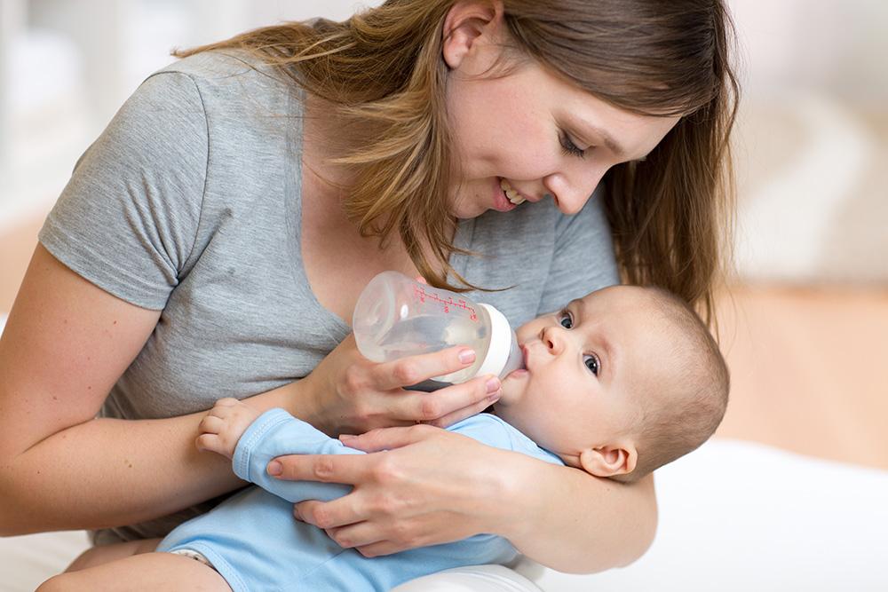assistante maternelle qui donne le biberon à un bébé