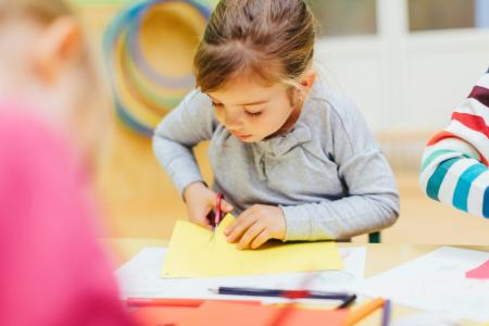 petite fille fait du découpage en classe maternelle