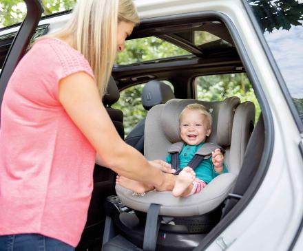 Une maman installe son enfant dans un siège auto