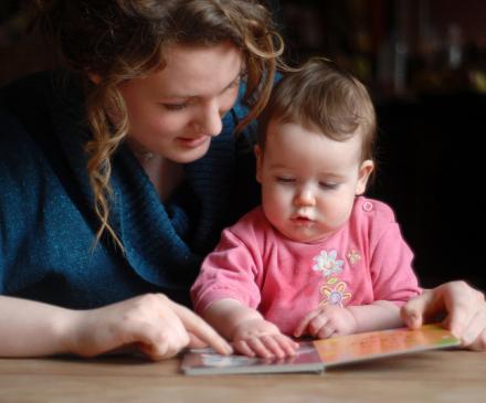 assistante maternelle regarde un livre avec un bébé