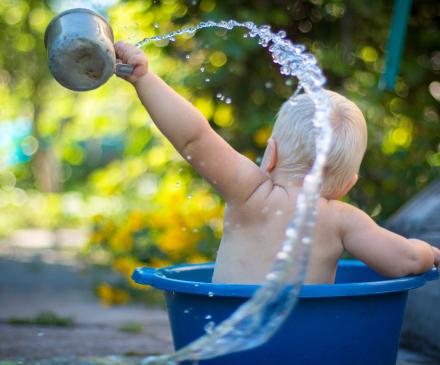 enfant joue avec l'eau