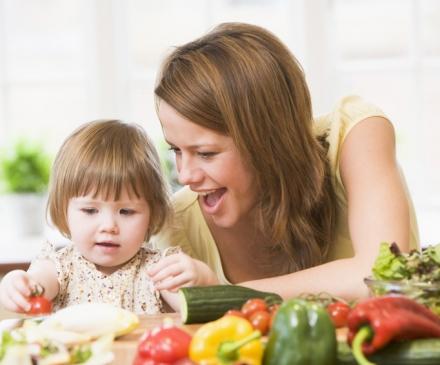 femme avec enfant devant des légumes frais