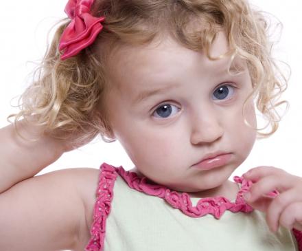 Enfant qui se gratte la tête à cause des poux