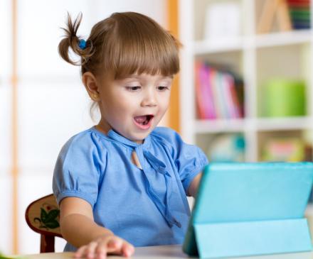 Une petite fille est sidérée devant une tablette