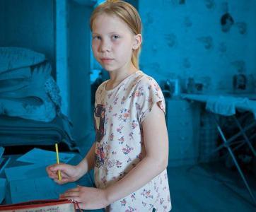 Une petite fille triste dans une chambre