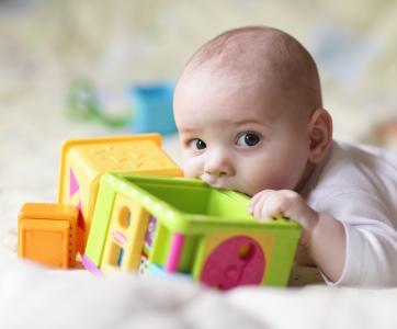 bébé qui mord dans un jouet