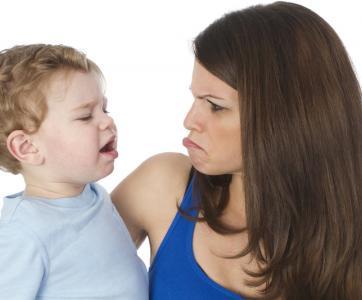 Un enfant boude dans les bras d'une femme qui l'imite