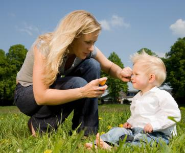 Une maman applique de la crème solaire sur le visage de son fils