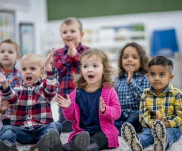 Groupe d'enfants de meternele qui tapent dans leur mains et chantent