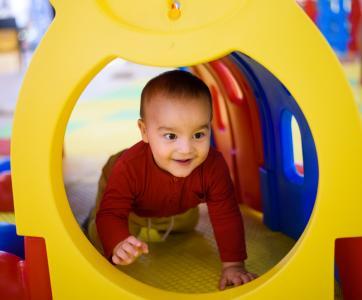 enfant joue dans tunnel  à la crèche