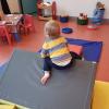 enfant qui bouge sur blocs de mousse dans lieu d'accueil