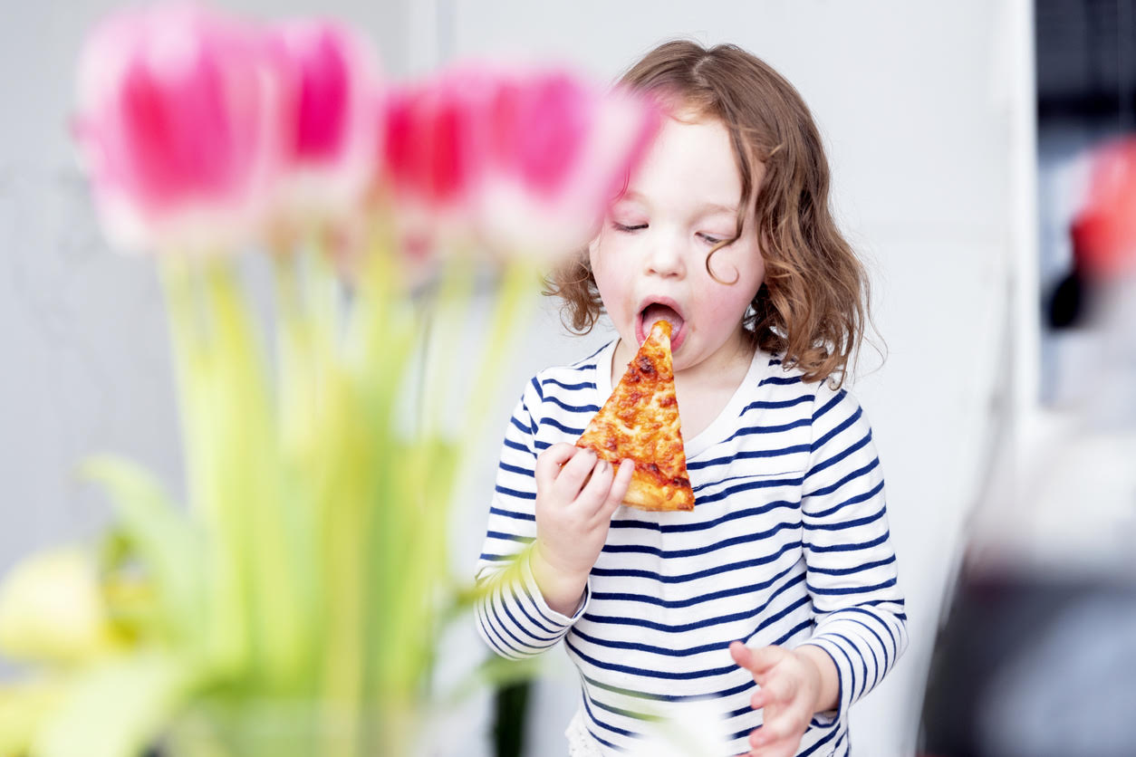 petite fille qui mange une pizza